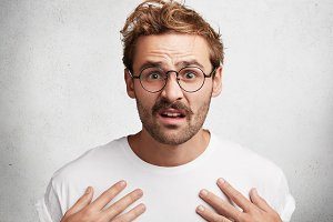 Indignant puzzled young bearded male with discontent expression, points at himself, wears casual white t shirt and spectacles, poses agianst white concrete wall. People and body language concept