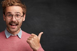Cheerful male nerd in spectacles stands against chalkboard, points with thumb on copy space for your advertising content. Horizontal shot of glad college professor shows something at blackboard
