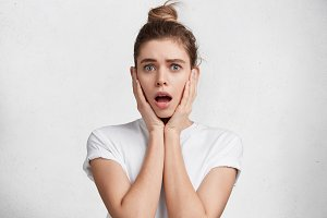 Surprised young pretty female has hair tied in knot, looks with opened mouth, shocked to see something awful, dressed casualy, isolated over white background. People, surprisment, facial expresions