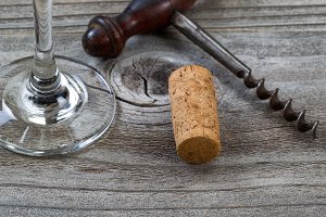 Used cork with corkscrew and glass