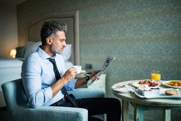 Mature businessman having breakfast…