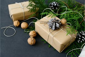 Wrapping rustic eco Christmas gifts with craft paper, string and natural fir branches on dark background