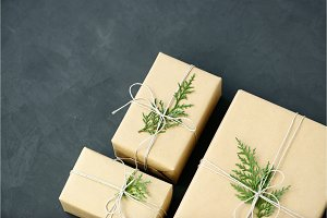 Lovely Holiday wrapping ideas rustic eco Christmas packages with brown paper, string and natural fir branches on dark background