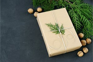 Wrapping rustic eco Christmas packages with brown paper, string and natural fir branches on dark background