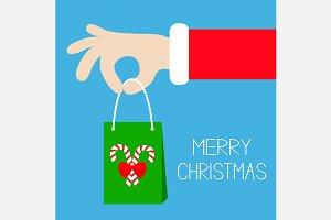 Santa Claus hand holding gift bag
