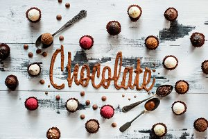 Word chocolate made from glazing with chocolates, candies and tea spoons on a white wooden background. Food typography concept.
