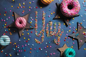 Exclamation Yay written with sprinkles on a stone background with donuts and stars. Party preparation concept.