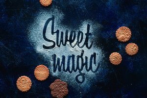 Words Sweet Magic made with flour. Cookies and sugar powder on a dark background. Food typography concept. Sweet flat lay.