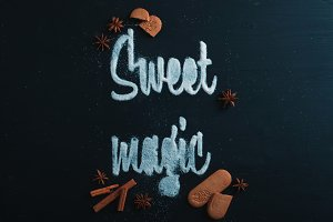 Words Sweet Magic made with sugar. Cookies and crumbs on a dark background. Food typography concept. Sweet flat lay.