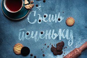 Words Eat a cookie made with sugar. Cookies, pin rolls, chocolate drops and tea cup on a concrete background. Food typography concept. Sweet flat lay.