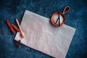 Wax paper with copy space on a dark marble background with vanilla, sugar and cinnamon. Baking food photography.