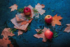 Rainy autumn still life with apples, fallen leaves, chess pieces and water drops on a stone background