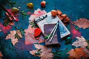 Rainy autumn still life with books, fallen leaves, drawing compasses, papers and water drops on a stone background