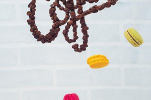 Coffee letters made with beans flying over espresso and macaroons. High key still life with levitation.