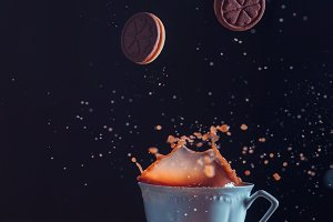 Porcelain tea cup with falling cookies and a splash on a dark background. Frozen motion food photography.