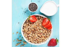 bowl with muesli, fresh strowberry, chia seeds and milk in milk jug