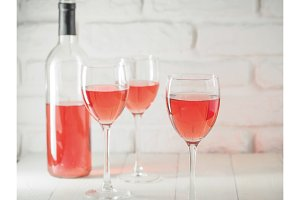 Three wineglass with pink wine and bottle on white brick wall background