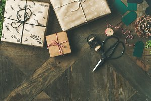Flat-lay of gift boxes, rope, fur branches, scissors, pine cones