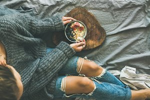 Woman in grey sweater and jeans eating rice coconut porridge