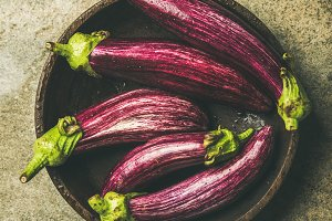 Flat-lay of fresh raw Fall harvest purple eggplants, square crop
