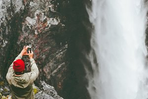 Traveling Man taking photo waterfall