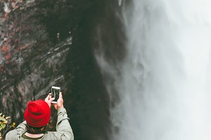Man taking photo of waterfall