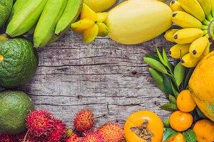 Colorful fruits on the white wooden table, Bananas, carambola, mango, papaya, mandarin, rambutan, pamela, copy space for text