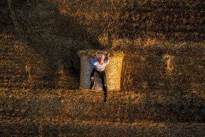 Young man enjoys sunset at the top of a hay bale