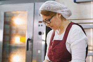 Adult woman in glasses and apron bakes cakes in the bakery