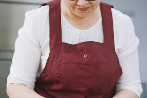 Adult woman in glasses and apron bakes cakes in the bakery face