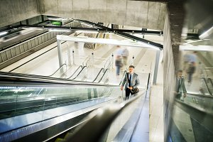 Businessman on an escalator on a metro station.