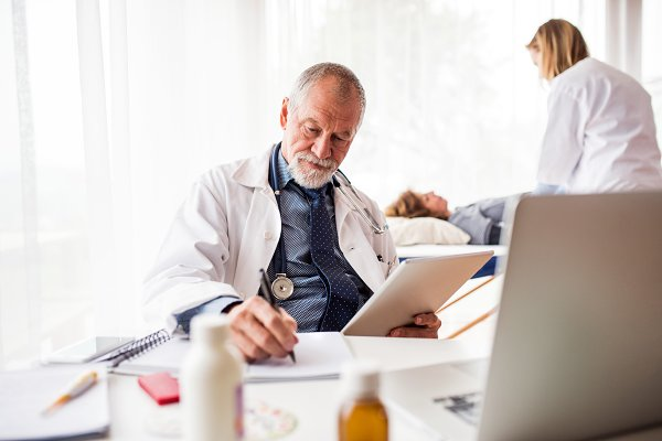 Senior doctor with tablet in his of…