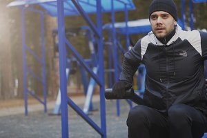 Young athlete man doing exercise at outdoor gym in winter park