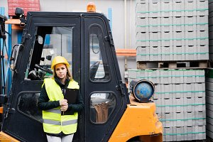 Woman forklift truck driver in an industrial area.