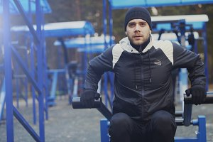 Tilt up of Young athlete man doing exercise at outdoor gym in winter park
