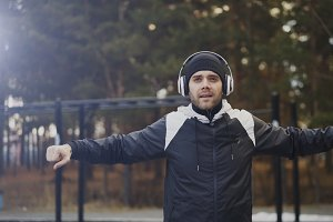 Handsome man in headphones doing warm-up exercise while listening music in winter park