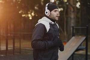 Attractive man in headphones doing warm-up exercise preparing for jogging while listening music in winter park