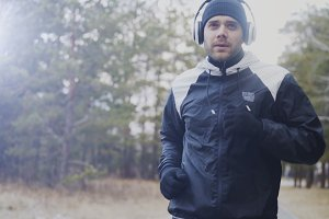 Attractive runner man in headphones jogging while listening music in winter park in the morning