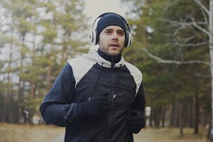 Handsome runner man in headphones jogging while listening music in winter park in the morning