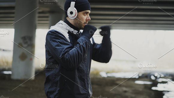 sportive man boxer in headphones doing boxing exercise in urban location outdoors in winter