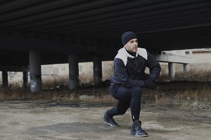 Attractive man runner doing stretching exercise for morning workout and jogging at urban location outdoors in winter