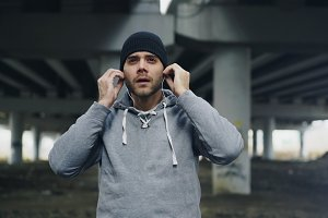 Handsome sportive man runner putting on earphones and starts running at urban outdoors city location in winter