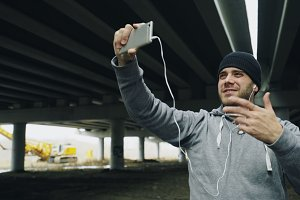 Boxer man having video chat on smartphone with friends after workout at urban location outdoors in winter
