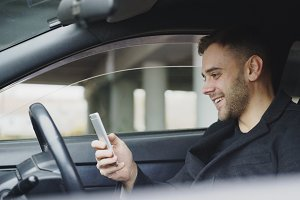 Attractive businessman sitting inside car laughing while using smartphone after trip