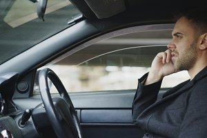 Stressed businessman swearing and talking phone while sitting inside car outdoors