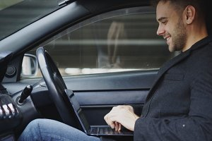 Attractive smiling man typing laptop computer while sitting inside his car outdoors
