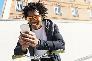 Afro young man using mobile.