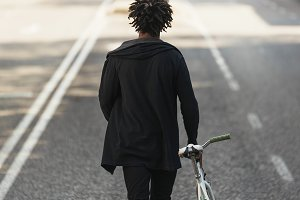 Afro man walking with his bike.