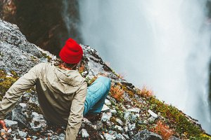 Man tourist on cliff at waterfall
