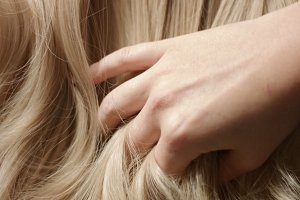 Woman's hand running through hair